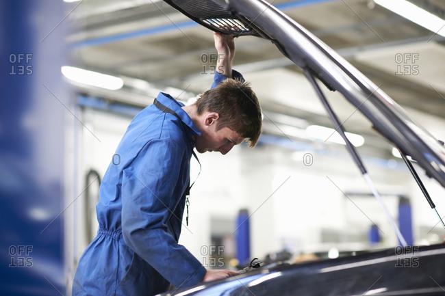 College mechanic student inspecting under car hood in repair garage