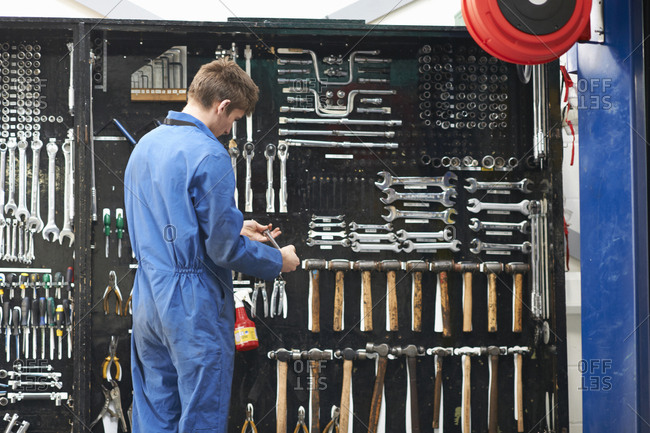 College mechanic student selecting wrench from repair garage tool kit