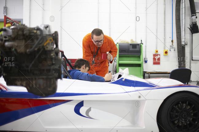 College mechanic students checking racing car in repair garage