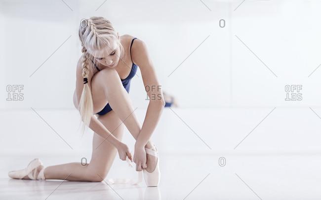 Young female ballet dancer kneeling in dance studio tying ballet slipper