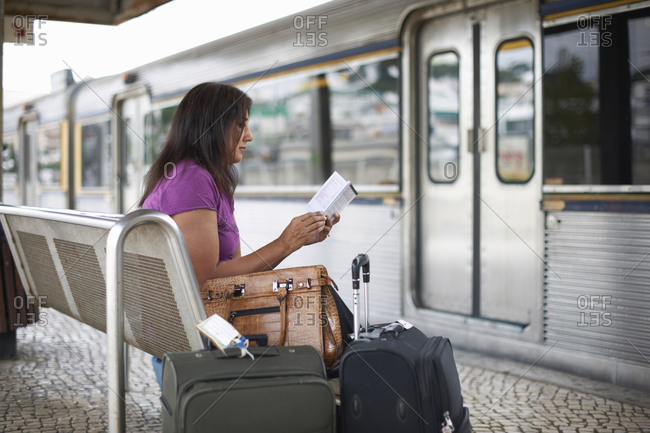 Mature woman waiting on train platform reading guidebook