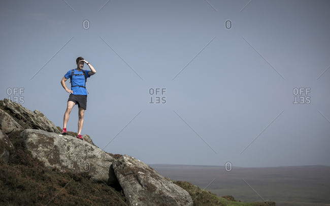 Male runner looking out from Stanage Edge, Peak District, Derbyshire, UK