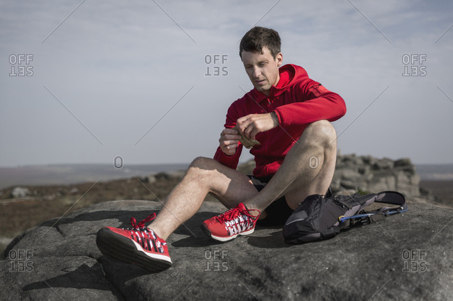 Male runner opening snacks on top of Stanage Edge, Peak District, Derbyshire, UK