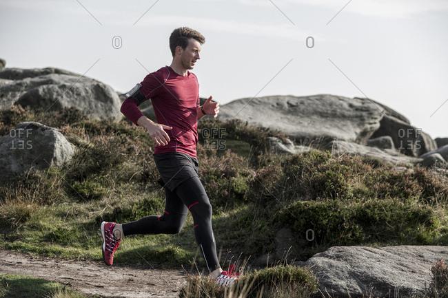 Male runner running down path from Stanage Edge, Peak District, Derbyshire, UK