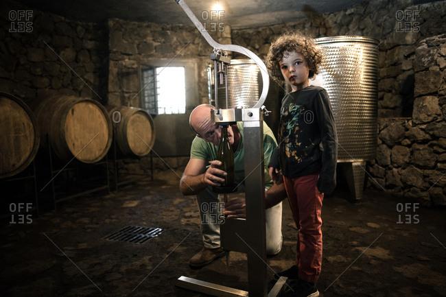 Boy with winemaker corking wine bottle in cellar