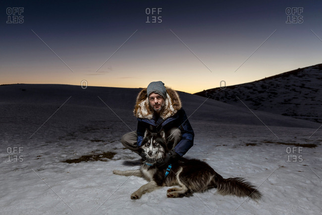 Portrait of mature man crouching with dog in snow at night