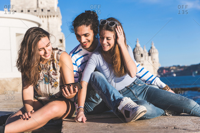 Three friends, sitting on wall by sea, Belem Tower in background, Lisbon, Portugal