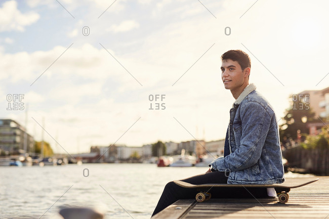 Young man sitting by river, skateboard beside him, Bristol, UK