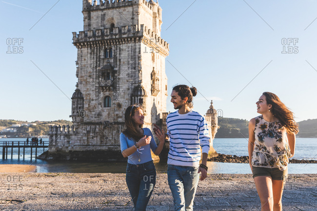 Three friends, walking on beach, Belem Tower in background, Lisbon, Portugal