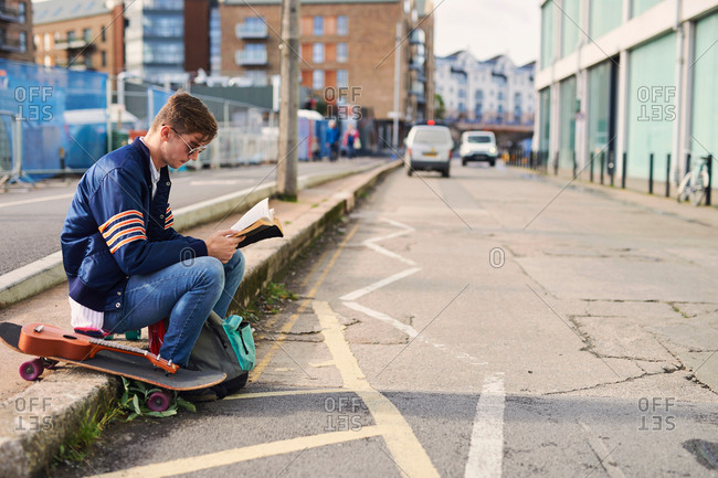 Young man sitting on kerb, reading book, skateboard beside him, Bristol, UK