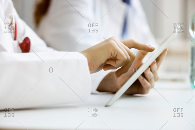 Doctor using digital tablet, close-up