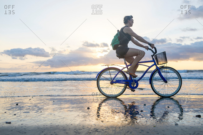 Woman cycling on beach at sunset, Nosara, Guanacaste Province, Costa Rica