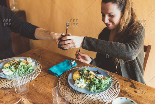 Couple handing jar over lunch table