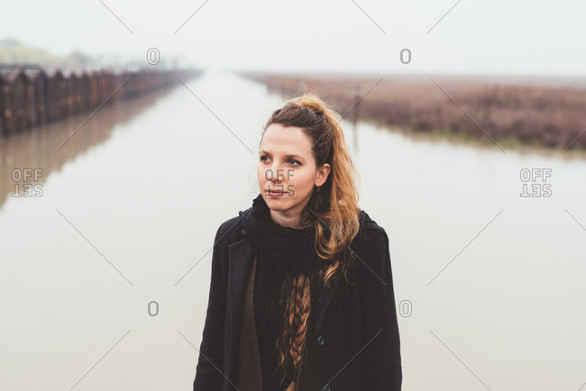 Portrait of young woman on misty canal waterfront