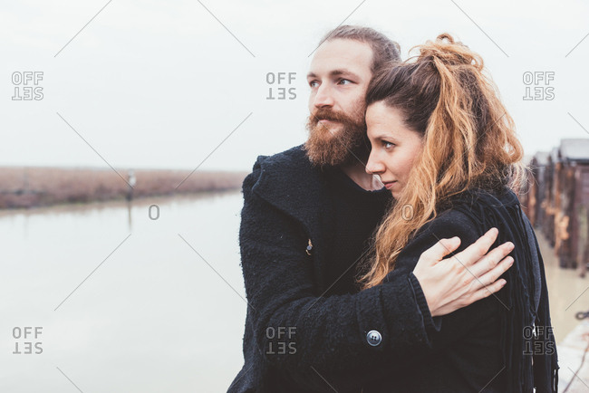Couple hugging on misty canal waterfront