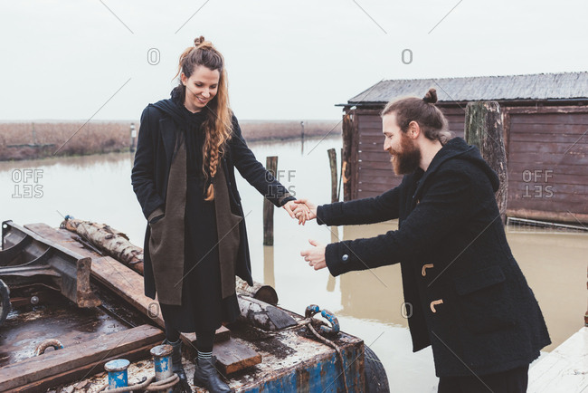 Man helping girlfriend from barge on canal waterfront