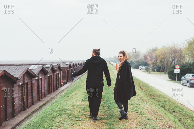 Rear view of couple strolling on embankment