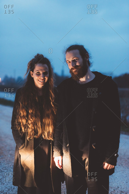 Portrait of couple on roadside at dusk