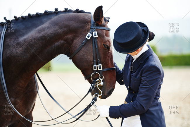 Female rider petting dressage horse in equestrian arena