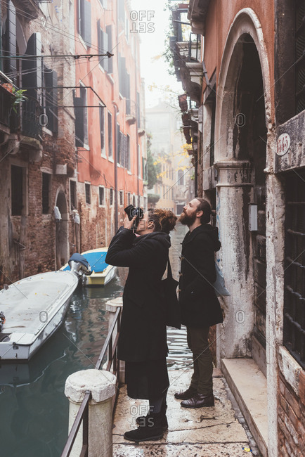 Couple photographing building exteriors from canal waterfront, Venice, Italy