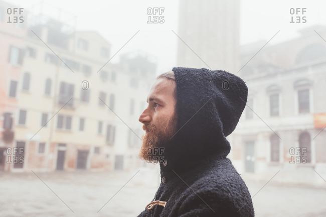 Portrait of man in hood in misty , Venice, Italy