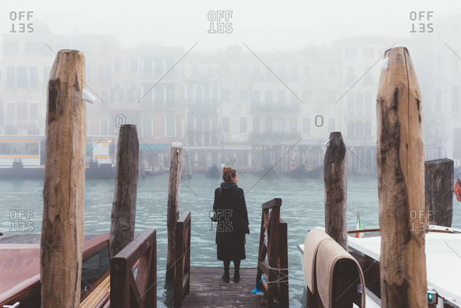 Rear view of woman looking out from misty canal pier, Venice, Italy
