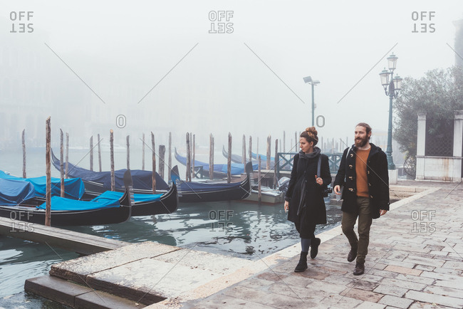 Couple strolling along misty canal waterfront, Venice, Italy
