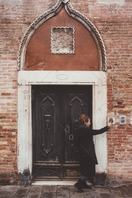 Young woman ringing doorbell of old building, Venice, Italy