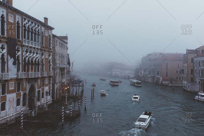 Venice, Italy - 20/11/2016: Elevated view of motor boats on misty canal, Venice, Italy