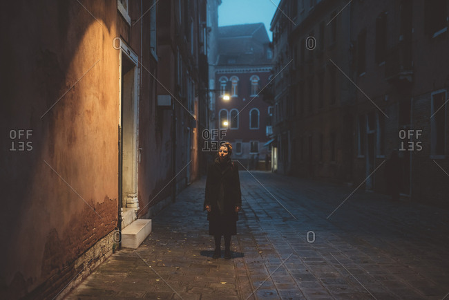 Portrait of young woman standing in street at dusk, Venice, Italy