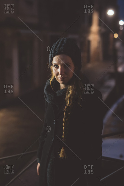 Portrait of young woman in knit hat at night, Venice, Italy
