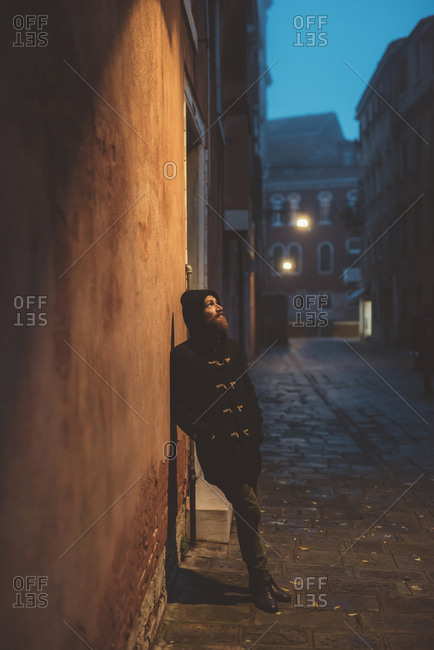 Portrait of man leaning against street wall at dusk, Venice, Italy