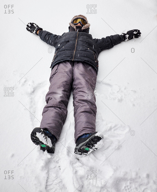 Boy lying on back on snow-covered ground