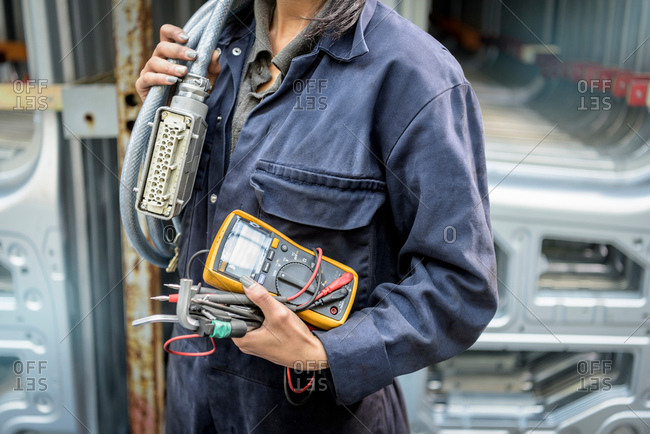 Female apprentice electrician holding equipment in car factory, close up