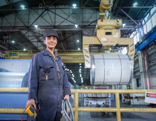 Female apprentice electrician in car factory, portrait