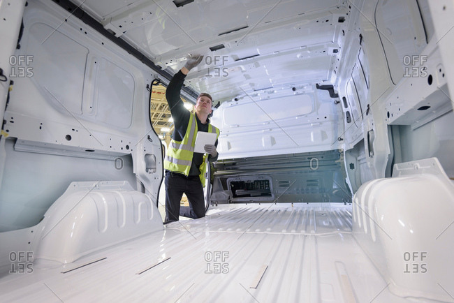Apprentice vehicle inspector inspecting interior of vehicle in car factory