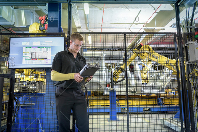 Apprentice engineer operating robots on production line in car factory