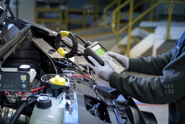 Female apprentice engineer testing car on production line in car factory, close up