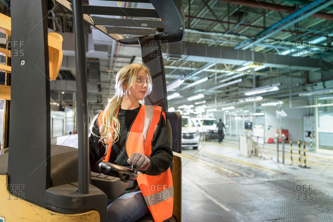 Female forklift driver in car factory