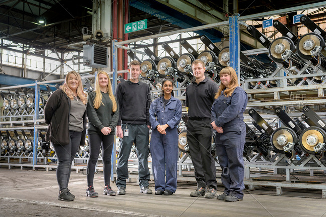 Group portrait of male and female apprentices in car factory