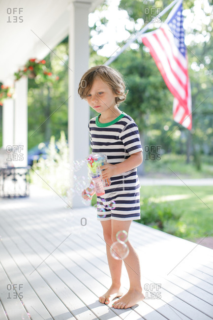Boy making bubbles from toy bubble maker on porch
