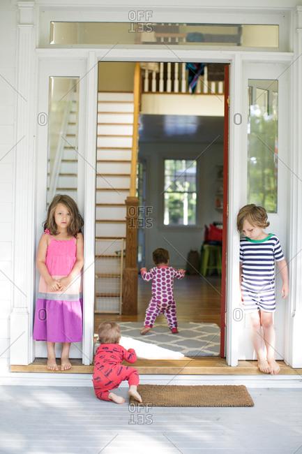 Boy and girl watching toddler crawling in house doorway