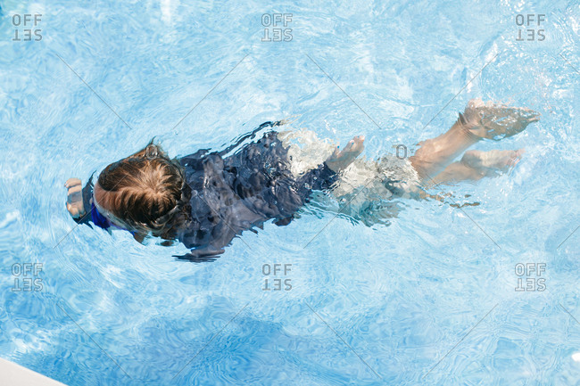 Overhead view of boy swimming in outdoor swimming pool