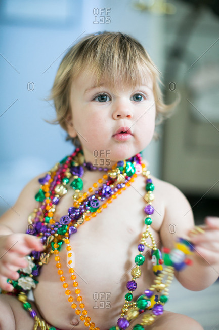 Female toddler trying on bead necklaces in kitchen