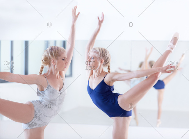 Two female ballet dancers dancing face to face in dance studio