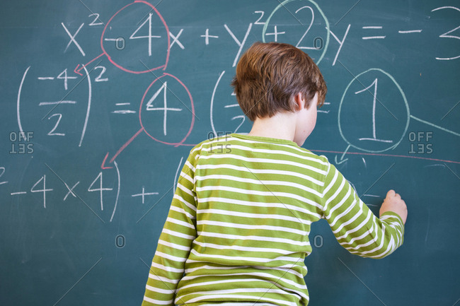 Rear view of primary schoolboy answering equation on classroom blackboard