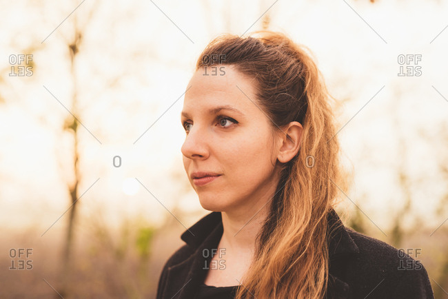 Young woman gazing in misty woodland
