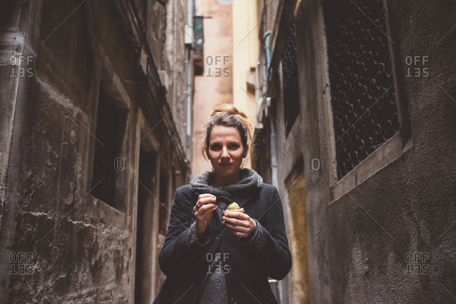 Portrait of young woman eating gelato in dark alley, Venice, Italy