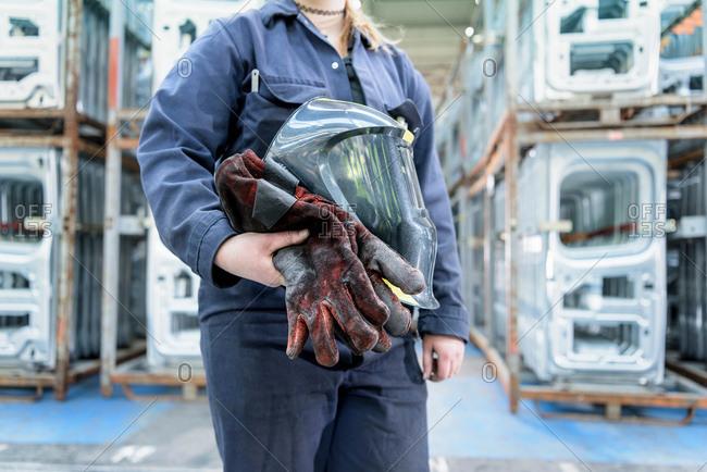 Female apprentice welder holding equipment in car factory