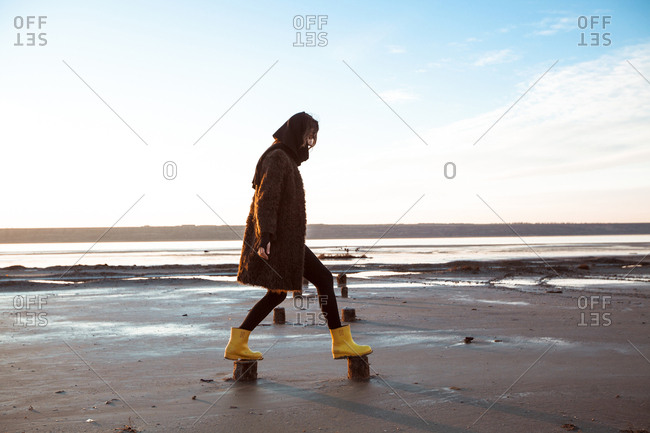 Woman balancing on wooden stumps on beach
